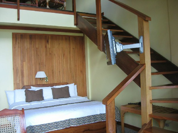 A Family Suite with stairs to a mezzanine with an additional King Bed at El Establo hotel.