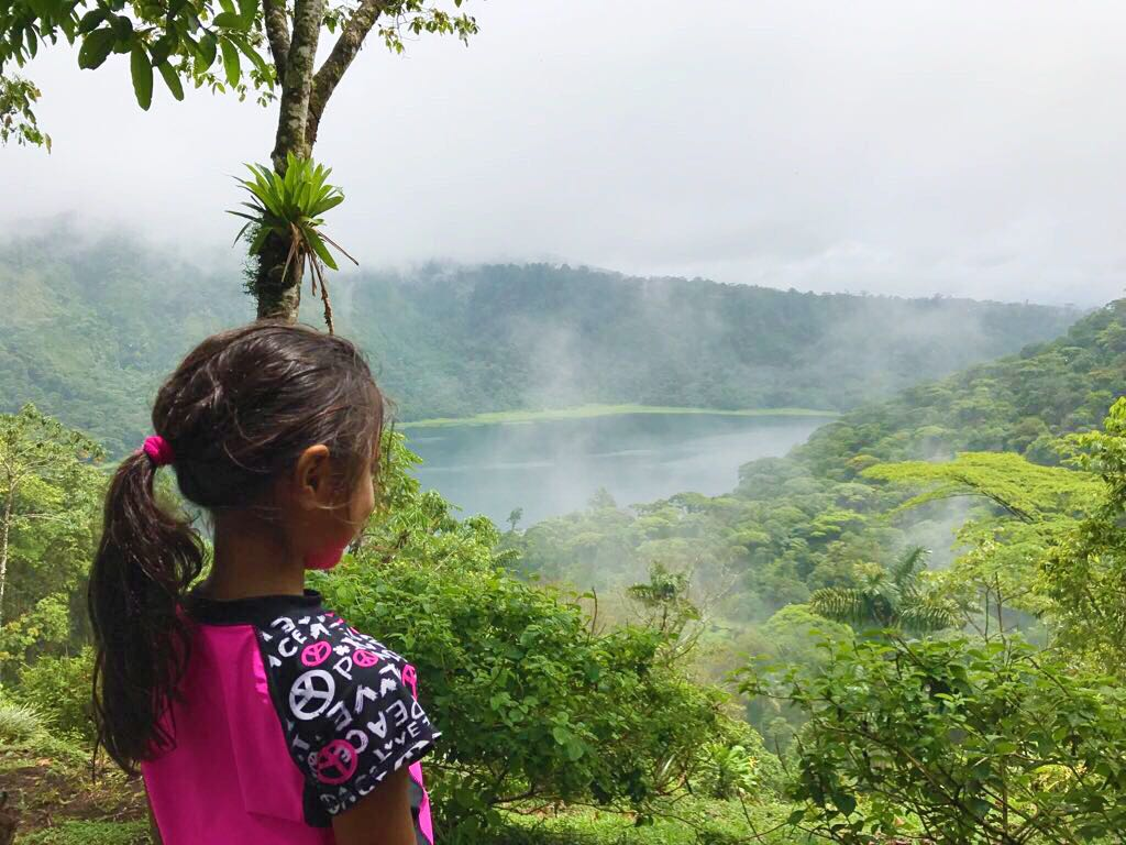A young girl overlooking the vibrant nature of the Costa Rican mountains