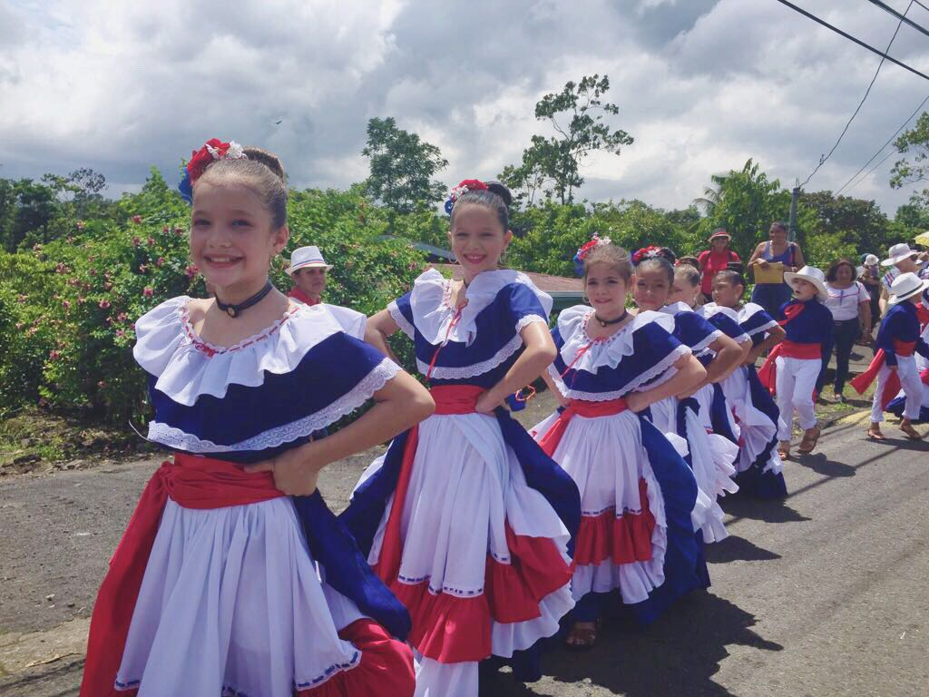 A line of women wearing one of the many colorful and vibrant national dresses of Costa Rica